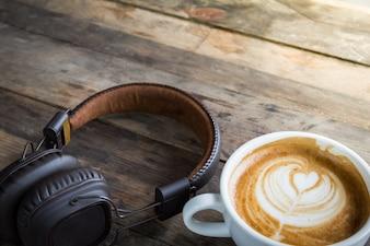Latte koffiekopje en koptelefoon op houten tafel