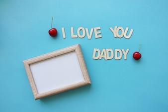 Leeg frame en kersen op blauw oppervlak voor Vaderdag