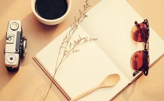 Leeg notitieboekje en filmcamera met zonnebril, vintage filter effect