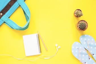 Leeg notitieboekje, oortelefoons, cactus met vrouwelijke objecten op gele achtergrond met kopie ruimte