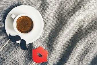 Lekkere koffie espresso in kleine kopje op grijze plaid met snor en lippen. Home Gezinsconcept. Top View.