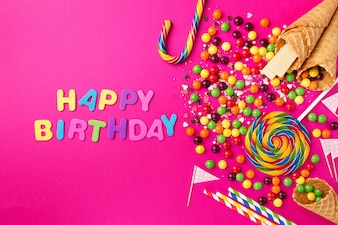 Lekkere smakelijke partijtoebehoren Gelukkige verjaardag op heldere roze achtergrond