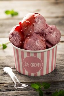 Lekkere smakelijke vanille aardbei ijs met jam in roze papieren beker op houten tafel. Detailopname.