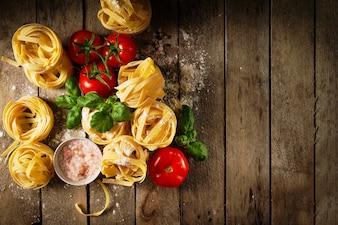 Lekkere verse kleurrijke ingrediënten voor het koken van pasta Tagliatelle met verse basilicum en tomaten. Bovenaanzicht. Houten Tafelachtergrond.