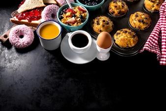 Lekkere verse ontbijt ingrediënten op zwarte donkere achtergrond. Klaar om te koken. Thuis Gezond Voedsel Koken Concept. Ruimte kopiëren. Toning.