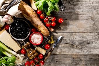Lekkere verse smakelijke Italiaanse ingrediënten voor het koken op oude rustieke houten achtergrond.