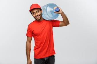 Leveringsconcept - Knappe Afro-Amerikaanse leveringsman met watertank. Geïsoleerd op grijze studio achtergrond. Ruimte kopiëren.