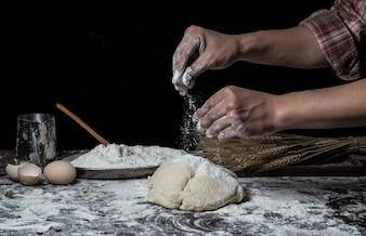 Man bereidt brooddeeg op houten tafel in een bakker close-up