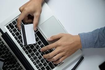 Man die creditcard in de hand houdt en beveiligingscode invoert met behulp van een laptop toetsenbord