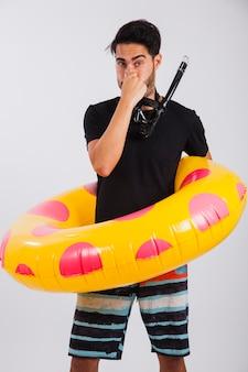 Man in zomer slijtage met drijvende buis vasthoudende neus