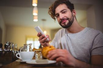 Man met behulp van mobiele telefoon terwijl het hebben van croissant in cafà ©