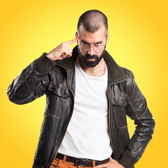 Man met een lederen jas aan het denken op een kleurrijke achtergrond