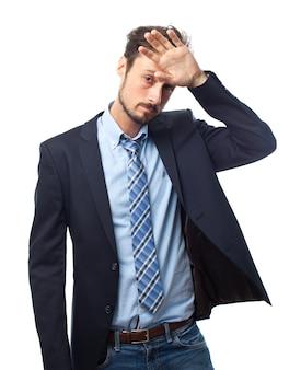 Man met pak met een hand op het voorhoofd