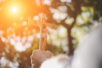Mannelijke handen die houten jesus houden, kruisen in de lucht met de natuurachtergrond.