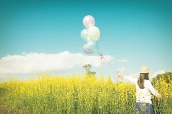 Meisje dat op het veld van gele flowerwith ballonnen loopt bij zonsondergang. Gelukkige vrouw op de natuur, concept over zorgeloze luchtigheid en ontspannen, vintage effect