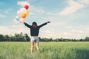 Meisje in een veld met ballonnen