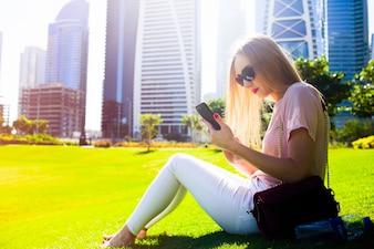 Meisje in roze shirt en witte jeans controleert haar telefoon op het gras in het park zitten
