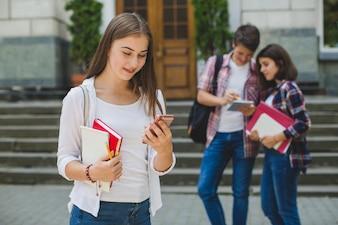 Meisje met telefoon en klasgenoten op straat