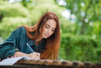 Meisje schrijven in notitieblok op tafel