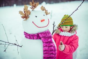 Meisje speelt met een sneeuw man