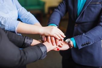 Mensen die in kantoor staan, houden handen in elkaar