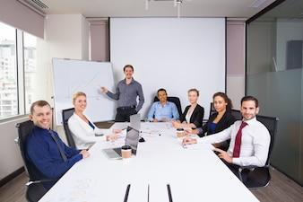 Mensen uit het bedrijfsleven poseren lachend in een vergaderruimte