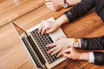 Mensen zitten aan bureau werken op laptop