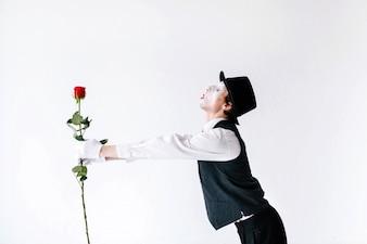 Mime strekt zijn handen uit met rode roos