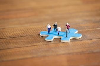 Miniatuur mensen op een puzzel
