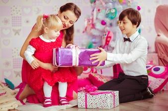 Moeder en kinderen openen kerstcadeaus