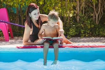Moeder en zoon zitten bij zwembad lezen