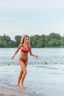 Mooi blond meisje dat op het strand loopt
