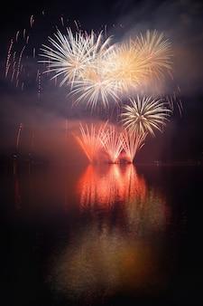 Mooi kleurrijk vuurwerk op het wateroppervlak met een schone zwarte achtergrond. Leuk festival en internationale wedstrijd van Brandweerlieden van over de hele wereld Ignis Brunensis 2017. Brno Dam - Tsjechië.
