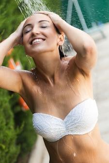 Mooi meisje in de zomerdouche in de buurt van het zwembad