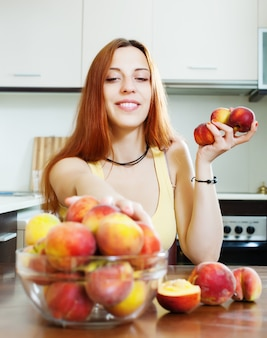 Mooi meisje in geel eet perziken