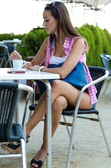 Mooi meisje met koffie op de straat.
