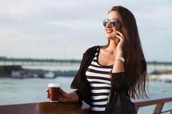 Mooie casual zakenvrouw op haar telefoon, meisje met koffie bij de zonsondergang van de rivier
