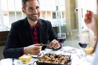 Mooie jonge man die blik kan eten in het restaurant.
