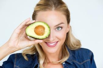 Mooie jonge vrouw die avocado in de keuken houdt.