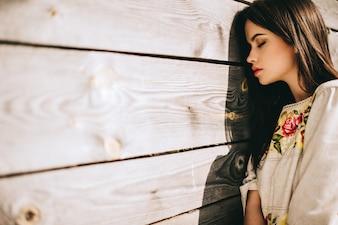 Mooie jonge vrouw die nationale Oekraïense kleding in houten hut draagt