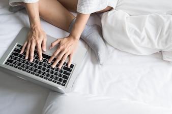 Mooie jonge vrouw in haar bed terwijl ze haar laptop thuis controleert.