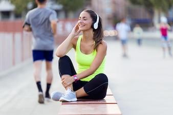 Mooie jonge vrouw luisteren naar muziek in de straat.