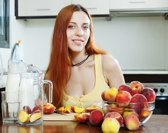 Mooie langharige vrouw koken met perziken