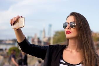 Mooie stedelijke vrouw genomen foto van zichzelf, selfie. Gefilterde afbeelding.