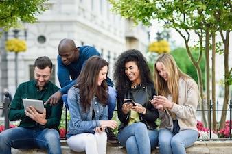 Multi-etnische jongeren die smartphone- en tabletcomputers gebruiken