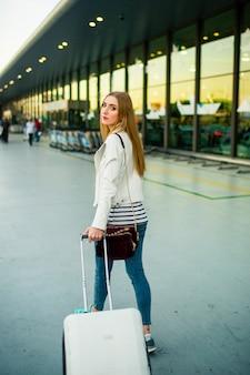 Nadenkende jonge vrouw loopt met een witte koffer langs de luchthaven