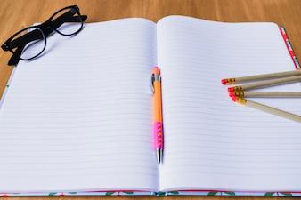 Open notitieboekje met potloden en glazen
