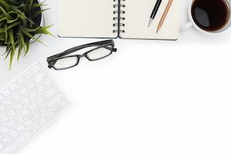 Open spiraal leeg notitieboekje en computer op wit bureau