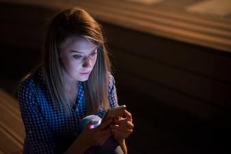 Opgetreden ongelukkige vrouw met mobiele telefoon geïsoleerd op grijze muur achtergrond. Droevig kijken meisje sms'en op smartphone