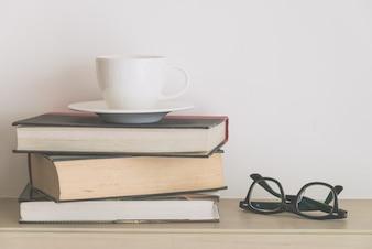 Oude boeken met een kop en een bril